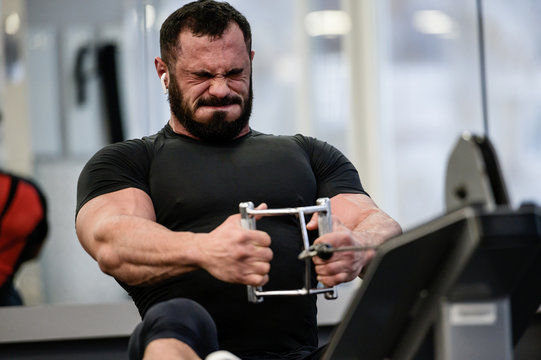 hard stress motivation sport workout training of bearded strong man with big muscles pulling weight on exercise equipment with grimace of pain and effort on face in gym