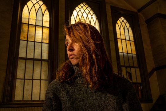 A young woman sits in a church with beautiful old stained glass