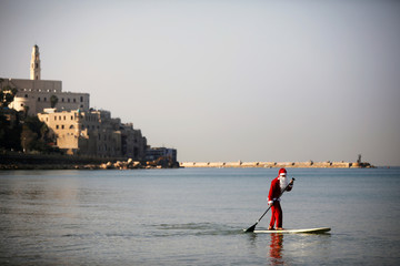 A man wearing a Santa Claus costume paddles on a SUP board in the Mediterranean Sea as Jaffa port  is seen in the background during an event organised by the Tel Aviv municipality, off the coast of Tel Aviv, Israel