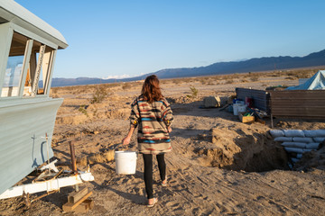 A woman carries a bucket of water in off grid living in the rugged desert outside Joshua Tree, California