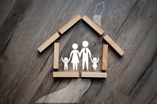 House made of wooden pieces with family stick figures on wooden background metaphor for dream of home ownership