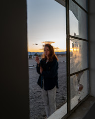 A stylish woman smokes a joint outside a window in the California desert at sunset