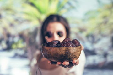 Woman in sunglasses holds out royal dates fruit in a bowl of coconut in a palm tree grove