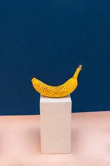 Yellow banana onn geometric plaster figure of the statue on a classic blue and pink-beige background