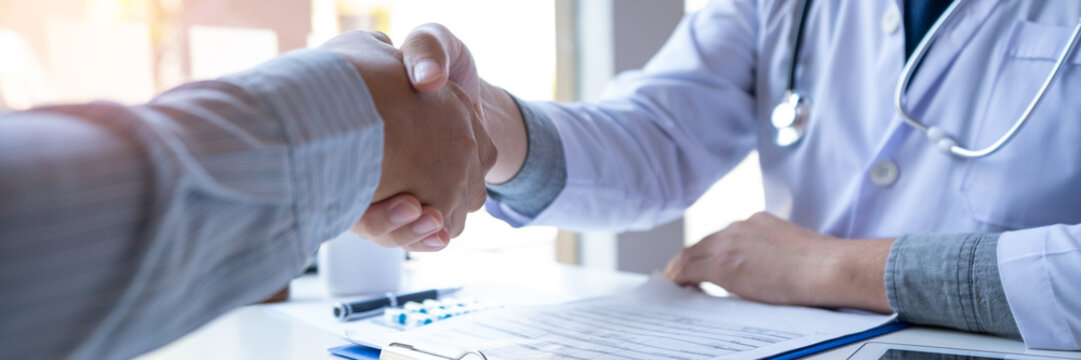 Medicine healthcare and trust concept, doctor shaking hands with patient colleague after talking about medical examination results.