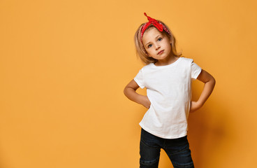 Beautiful little girl in a white T-shirt and a red bandage on her head with blue eyes looks slyly...
