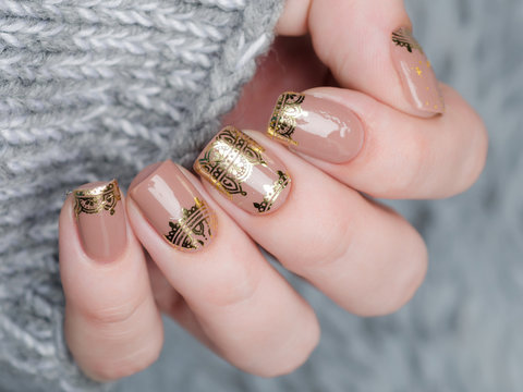 beige Nude manicure with gold lace pattern on a gray background