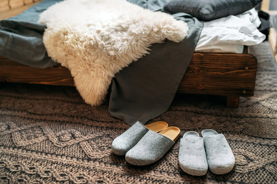 "The two pair of gray home slippers near the wooden bed on the ""knitted floor"" in the cozy bedroom. Home sweet home concept image."