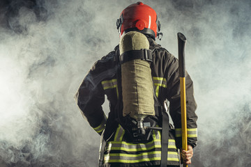 rear view on reverent, confident man working in fire station ready to save people from fire in emergency situations, wearing uniform and helmet