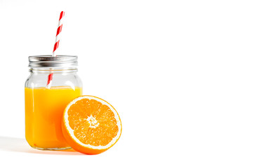 Poster Sap Glass jar with a tube with freshly squeezed orange juice stands on a white background next to fresh oranges