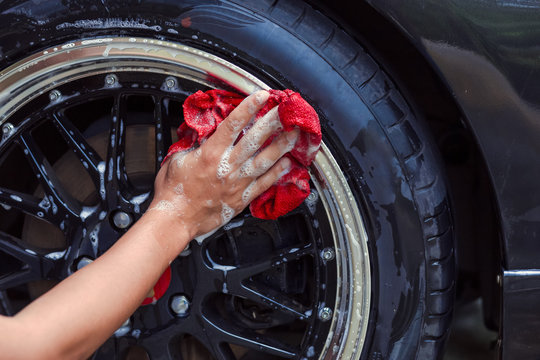 male hand with foam fabric washing car wheel Cleaning Wheels Use Water.