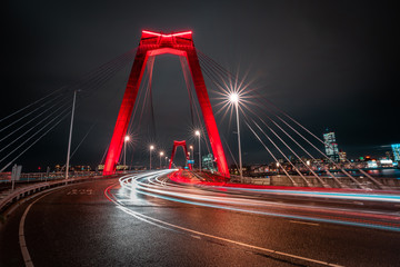 Photo sur Aluminium Rotterdam Light trails of traffic at the Willemsbrug in Rotterdam. Beautiful red bridge. Landmark of the skyline in Rotterdam, long exposure shot.