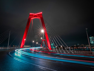 Fototapeten Rotterdam Light trails of traffic at the Willemsbrug in Rotterdam. Beautiful red bridge. Landmark of the skyline in Rotterdam, long exposure shot.