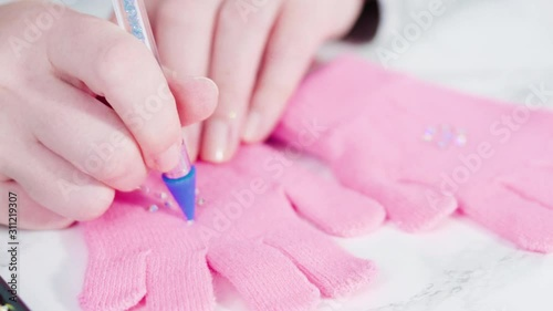 Wall mural Rhinestone pink kids gloves with snowflake shapes.