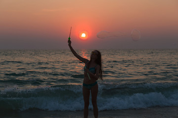 Young attractive girl blowing bubbles on the beach at sunset