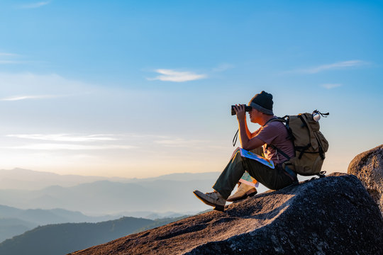 A young man with a lifted backpack looked in binoculars sitting on top of the mountain enjoying a spectacular view on the mountains above the clouds.