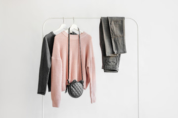 Female clothes in pastel pink and gray color on hanger on white background.  Jumper, shirt, jeans and bag. Spring/autumn outfit. Minimal concept.