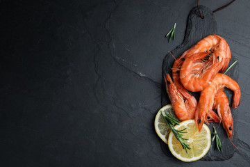 Delicious cooked shrimps with lemon and rosemary on black table, flat lay. Space for text