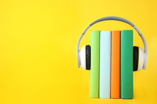 Books with modern headphones on yellow background. Space for text