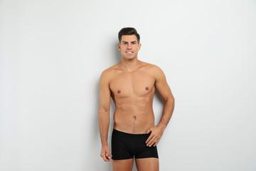 Handsome man in black underwear on white background