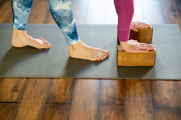 Women practicing yoga stretching using wooden blocks with hands, exercise for spine and shoulders flexibility