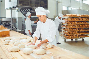 A woman baker smileswith colleagues at a bakery.