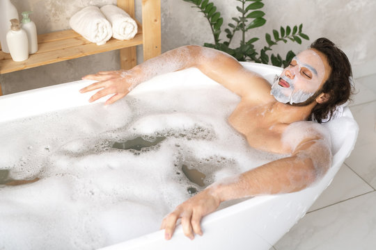 Serene young man with face mask relaxing in hot bath with foam
