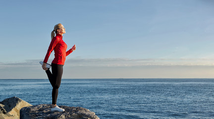 young caucasian woman doing sport crunches by the sea on the rocks