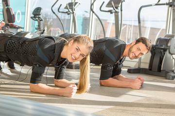 Man and woman doing electro muscular stimulation training in a modern gym