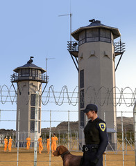 Prison yard with prisoners and security and two tall guard towers