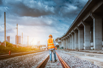 A senior engineer under inspection and checking construction process railway and checking work on railroad station platform .Engineer wearing safety uniform and safety helmet in work. Fotomurales
