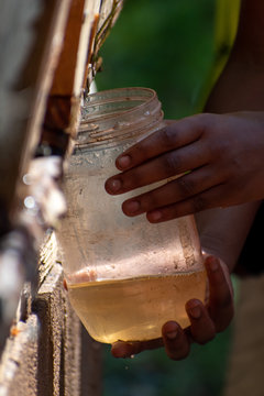 African American child holds up glass jars to gather dirty water draining. Picture taken in vertical, portrait orientation
