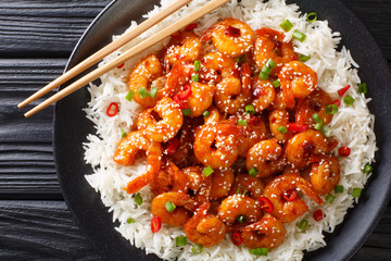 Tasty prawns with garlic, chili, sesame seeds and green onions served with rice close-up in a plate. Horizontal top view