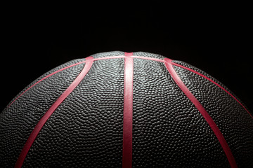 Close-up of black basketball on black background.