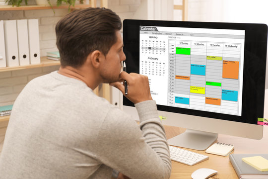 Handsome man using calendar app on computer in office