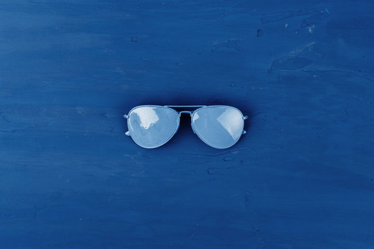 Blue aviator glasses on classic blue background, top view