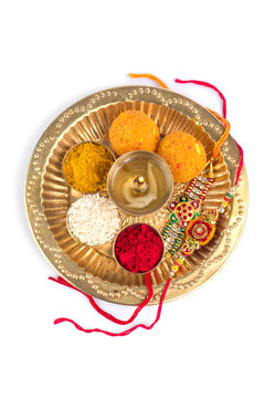 Indian Festival: Rakhi with rice grains, kumkum, sweets and diya on plate with an elegant Rakhi. A traditional Indian wrist band which is a symbol of love between Brothers and Sisters