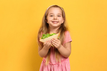 Poster Snack Cute little girl with tasty sandwich on yellow background