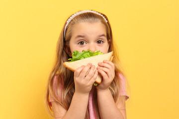 Cute little girl eating tasty sandwich on yellow background Fototapete