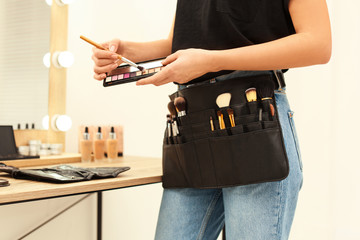 Professional makeup artist with eyeshadow palette and belt organizer full of tools in studio,...