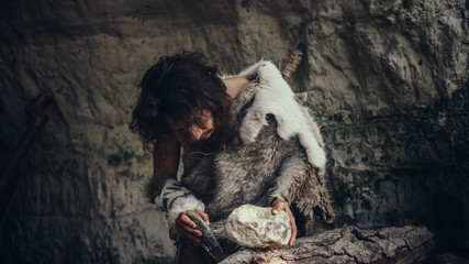 Primeval Caveman Wearing Animal Skin Hits Rock with Sharp Stone and Makes Primitive Tool for Hunting Animal Prey. Neanderthal Using Flint Rock to Create first Wheel. Wall mural