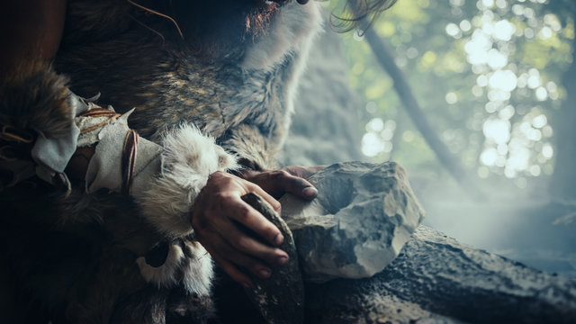 Closeup Shot of Primeval Caveman in Animal Skin Hits Rock with Sharp Stone, Makes First Primitive Tool for Hunting Animal Prey. Neanderthal Using Flint Rock. Dawn of Human Civilization.