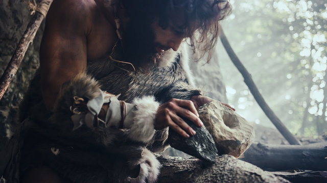 Primeval Caveman Wearing Animal Skin Hits Rock with Sharp Stone and Makes Primitive Tool for Hunting Animal Prey. Neanderthal Using Hand axe to Create first Wheel.