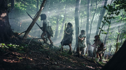 Fototapeta Tribe of Hunter-Gatherers Wearing Animal Skin Holding Stone Tipped Tools, Explore Prehistoric Forest in a Hunt for Animal Prey. Neanderthal Family Hunting in the Jungle or Migrating for Better Land obraz
