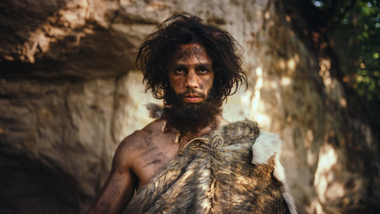 Portrait of Primeval Caveman Wearing Animal Skin Holding Stone Tipped Hammer. Prehistoric...