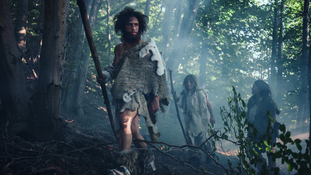 Tribe of Hunter-Gatherers Wearing Animal Skin Holding Stone Tipped Tools, Explore Prehistoric Forest in a Hunt for Animal Prey. Neanderthal Family Hunting in the Jungle or Migrating for Better Land