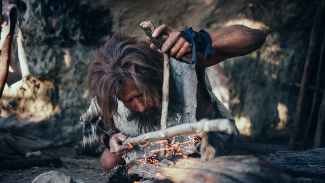 Close-up Shot of a Primeval Caveman Wearing Animal Skin Trying to make Fire with Bow Drill Method. Neanderthal Kindle First Man-Made fire in the Human Civilization History. Making Fire for Cooking.