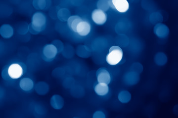 abstract blurred circular bokeh lights background toned in trendy Classic Blue color of the Year...