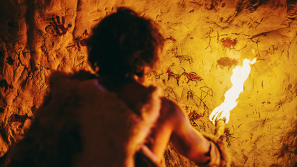 Fototapeta Primeval Caveman Wearing Animal Skin Standing in His Cave At Night, Holding Torch with Fire Looking at Drawings on the Walls at Night. Cave Art with Petroglyphs, Rock Paintings. Back View obraz