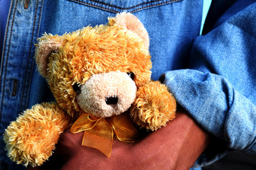 Picture of a brown teddy bear in a man's hand, dark tone